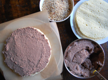 Assembly - cake stand with parchment strips, cake layers, Nutella mousse & chopped hazelnuts