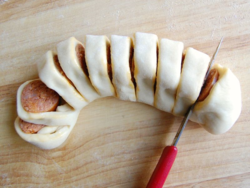 5) Wrap sausage in a piece of dough, cut through the sausage but leave the dough connected.